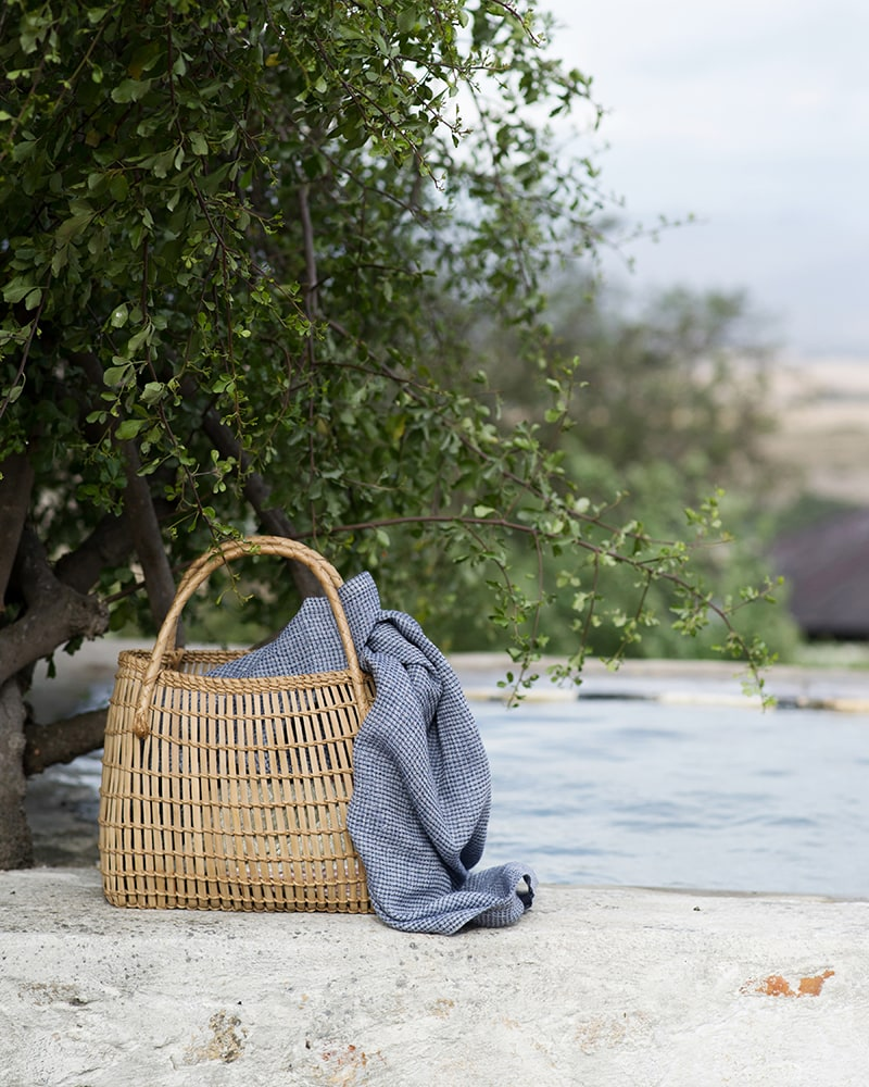 Mungo Cotton Dhow Towel in Block weave, featured in a basket by the pool in an outdoor scene. Textile is woven from all natural fibres at our mill in Plettenberg Bay, South Africa.