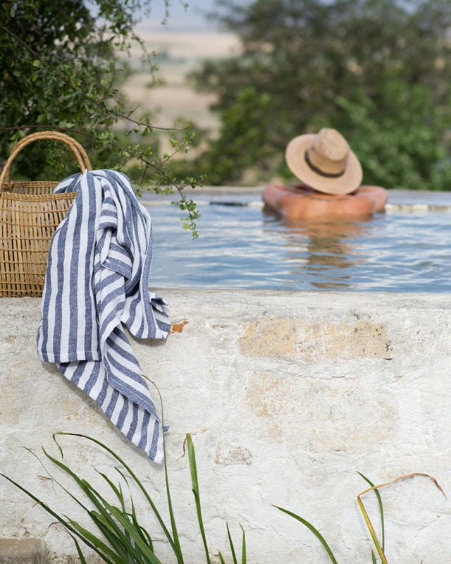 Mungo Cotton Dhow Towel in Stripe, featured in a basket by the pool in an outdoor scene. Textile is woven from all natural fibres at our mill in Plettenberg Bay, South Africa.