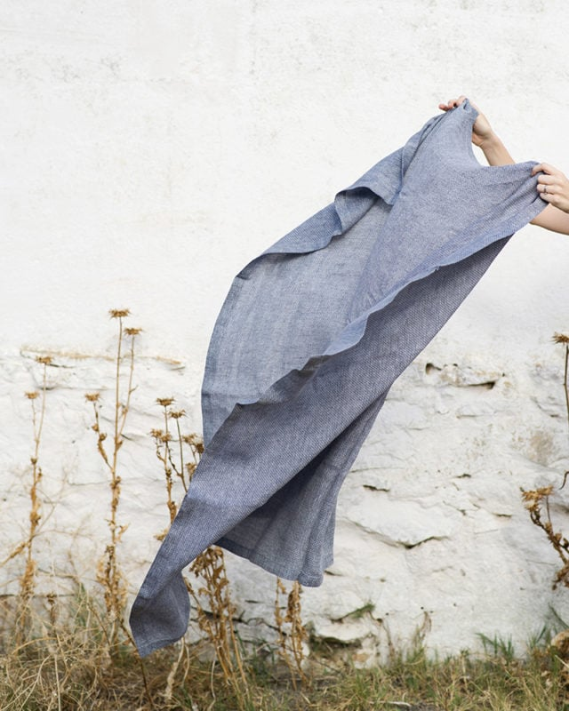 Mungo Cotton Dhow Towel in Diamond weave, blowing in the wind in an outdoor scene. Textile is woven from all natural fibres at our mill in Plettenberg Bay, South Africa.