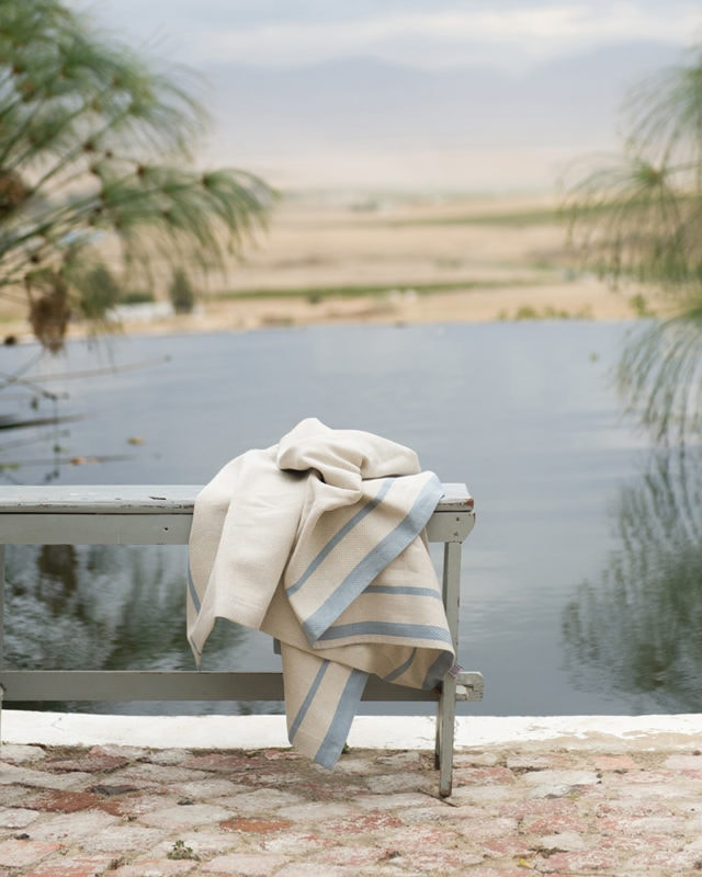 Mungo Cotton Huck Towel in Natural and Blue, featured on a bench by a dam in an outdoor scene in the Karoo.