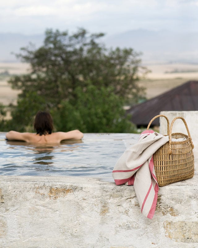 Mungo Cotton Huck Towel in Natural and Red, featured in a basket by the pool in an outdoor scene in the Karoo.