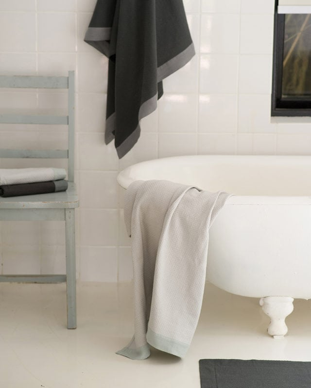 Mungo Cotton Interlace Towels in Charcoal with Metal Grey border and Stone with Moon Grey border, featured next to bathtub in a bathroom scene. Textile made from all natural fibres at our mill in Plettenberg Bay, South Africa.