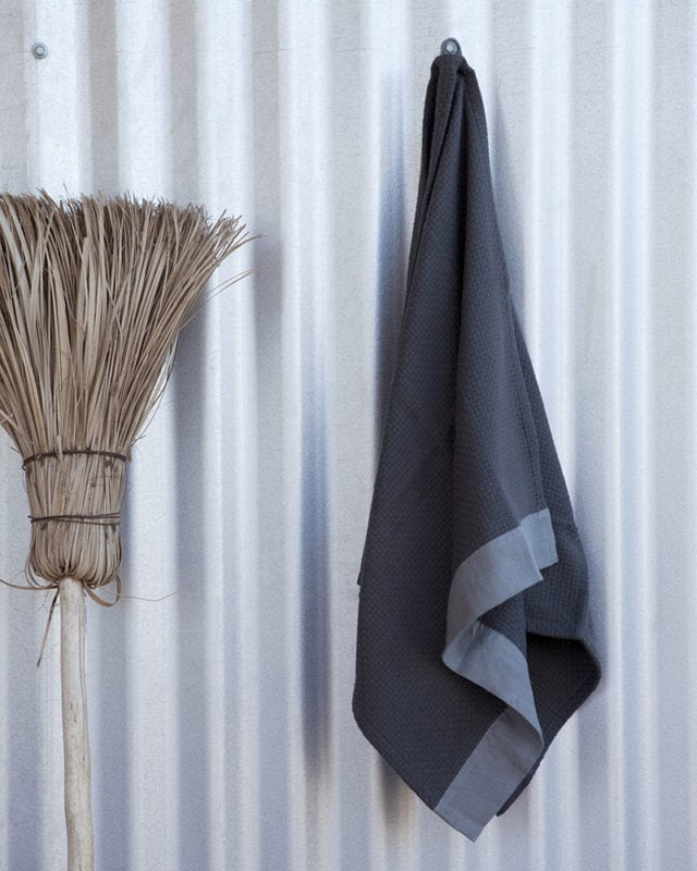 Mungo Cotton Interlace Towel in Charcoal with Metal Grey border, hanging with broom against corrugated iron sheet. Textile woven from all natural fibres at our mill in Plettenberg Bay, South Africa.