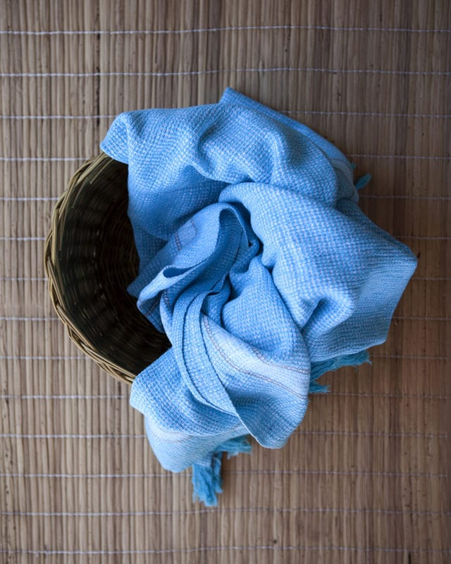 Mungo Summer Cotton Towel in Turquoise on a grass basket and mat. Textile woven from all natural fibres at our mill in Plettenberg Bay, South Africa.