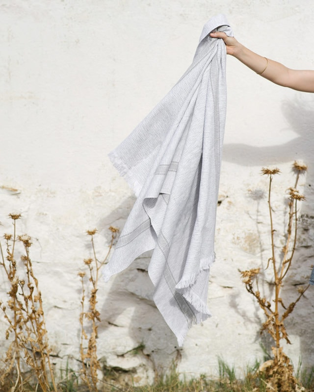 Hand holding the Mungo Summer Towel in Dove Grey, woven with all natural cotton fibre with eyelash fringe.
