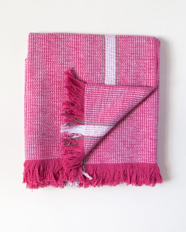 The Mungo Summer Towel in Hot Pink, folded in a square. Made with all natural fibres at our mill in Plettenberg Bay.