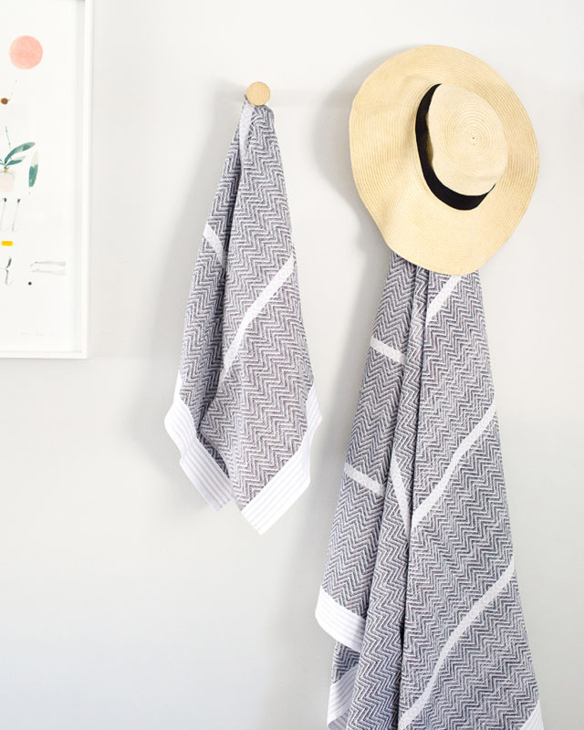 Mungo Tawulo Cotton Towels in Thunder Grey, hanging on wall with a hat. Textile woven from all natural fibres at our mill in Plettenberg Bay.