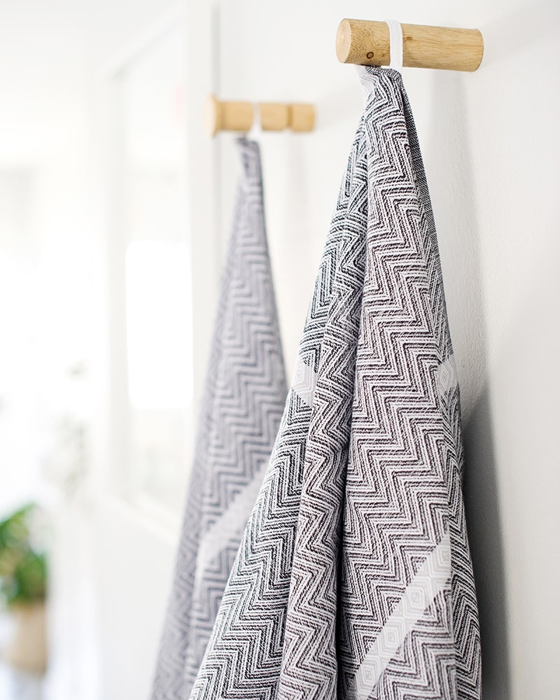 Mungo Tawulo Cotton Towels in Thunder Grey, hanging on pegs in bathroom scene. Textile woven from all natural fibres at our mill in Plettenberg Bay.