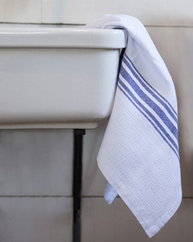 Mungo Willow Weave Cotton Towel in All Blue, hanging over porcelain basin in a bathroom scene. Woven from all natural fibres at our mill in Plettenberg Bay, South Africa.