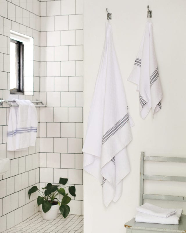 Mungo Willow Weave Cotton Towels in All Blue and Charcoal, featured in a tiled bathroom shower scene. Textile made with all natural fibres at our mill in Plettenberg Bay, South Africa.