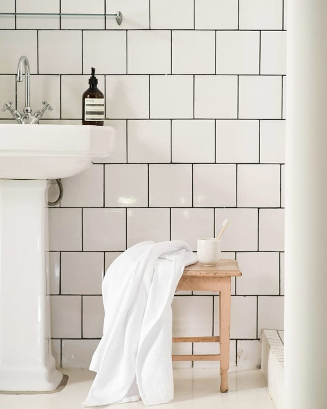 The Mungo Willow Weave Cotton Towel in White Stripe, featured in a tiled bathroom scene. Textile made with all natural fibres at our mill in Plettenberg Bay, South Africa.