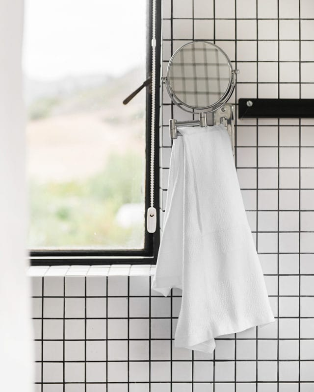 The Mungo Willow Weave Cotton Towel in White Stripe, hanging under bathroom mirror.