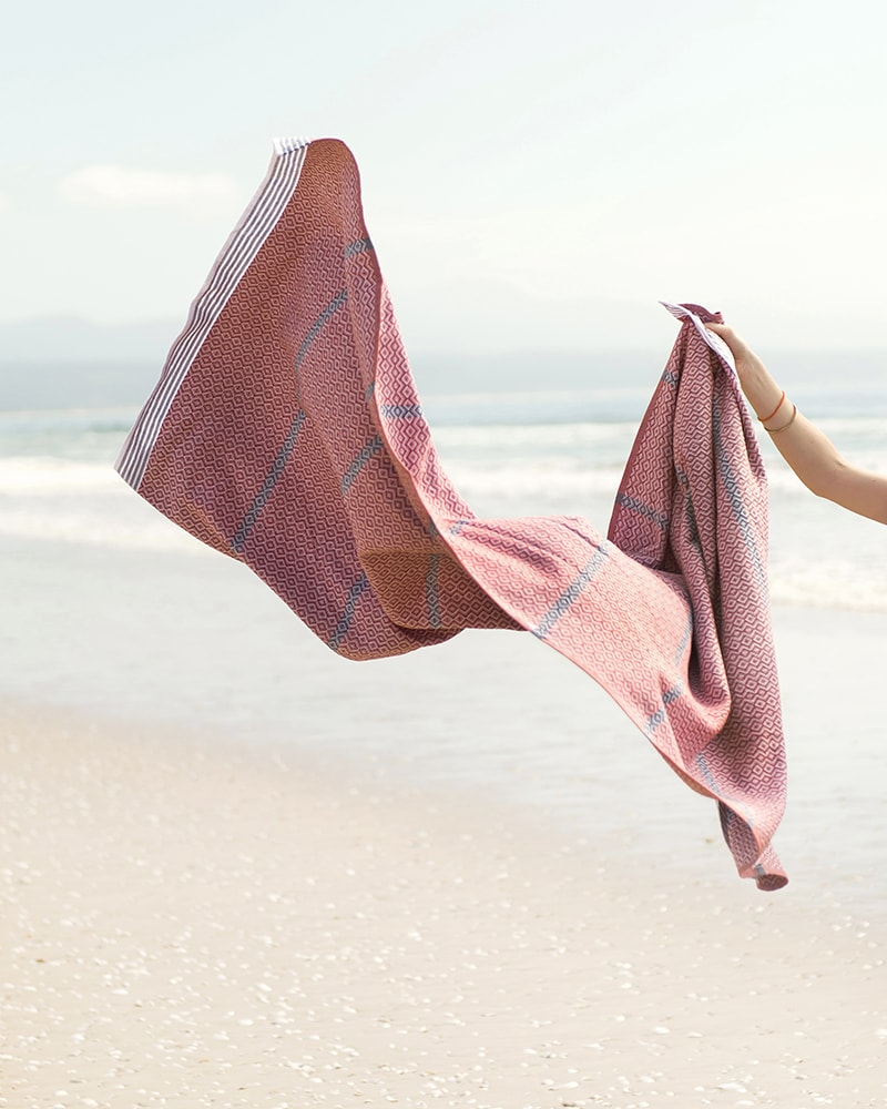Mungo Itawuli at the beach. A lightweight, soft and absorbent flatweave towel