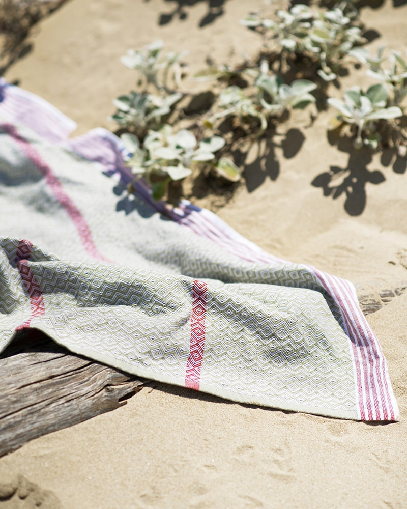 Mungo Itawuli at the beach. A lightweight, soft and absorbent flat weave towel