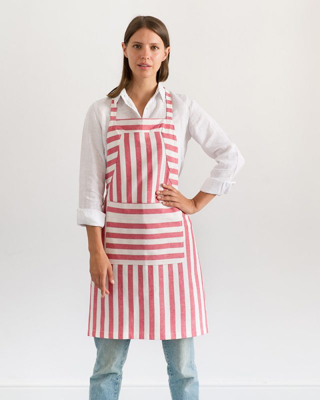 Woman wearing an all natural fibre Mungo Butcher Stripe Cotton Apron in White and Red, one of the items in our apparel range