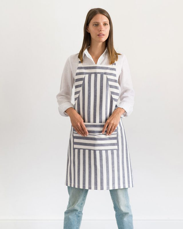 Woman wearing an all natural fibre Mungo Butcher Stripe Cotton Apron in White and Blue, one of the items in our apparel range