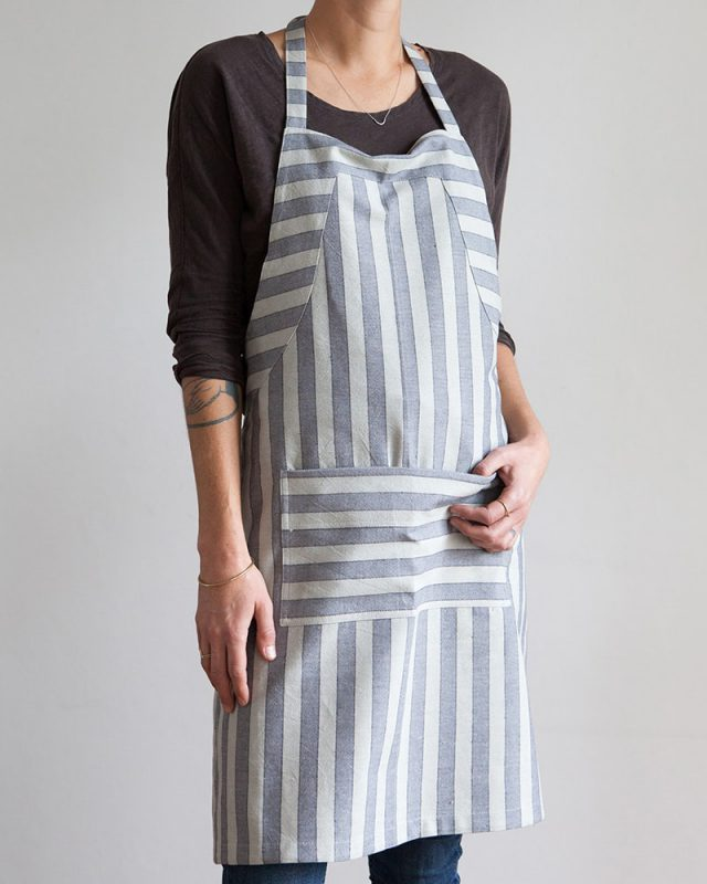 Woman wearing an all natural fibre Mungo Butcher Stripe Cotton Apron in Grey and Blue, one of the items in our apparel range