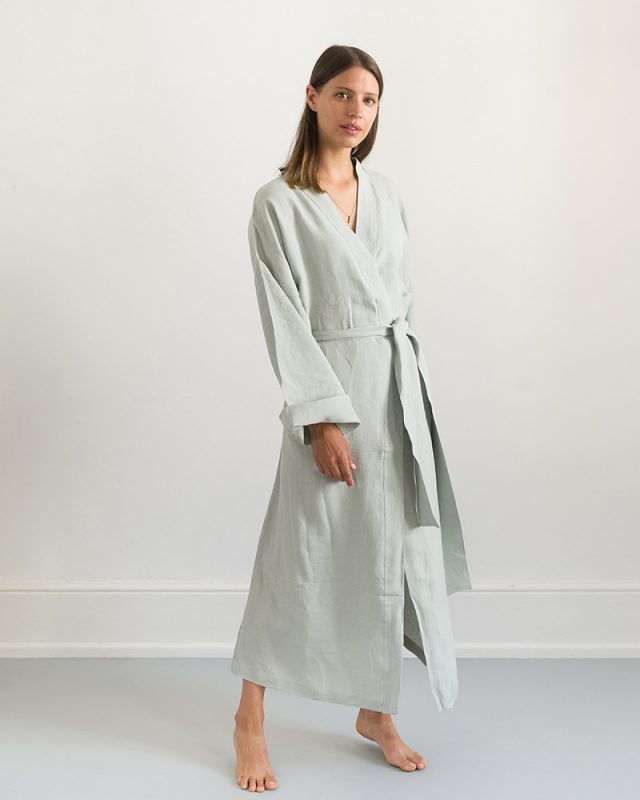 Woman wearing an all natural fibre Mungo Kamma Linen Gown in Moon Grey, one of the items in our apparel range.