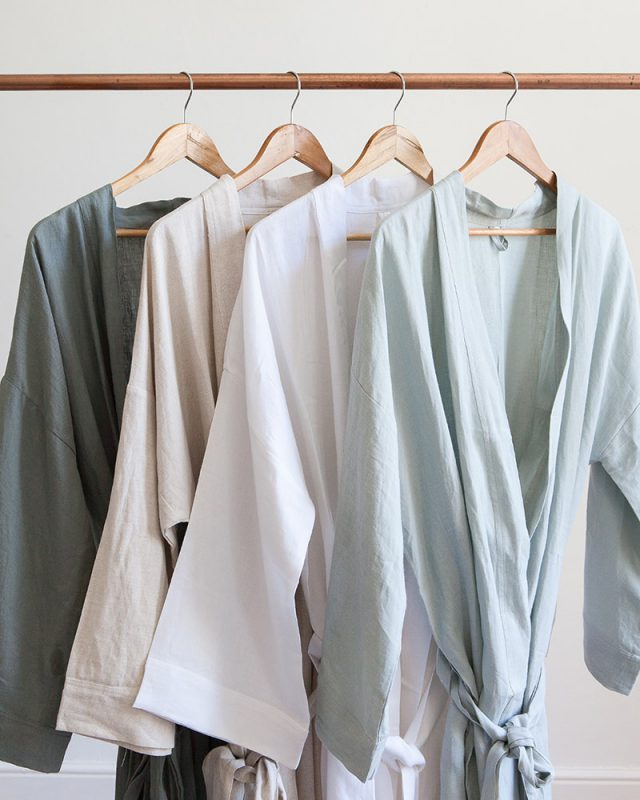 The all natural fibre Mungo Kamma Linen Gowns from our apparel range in fumo grey, white, natural and moon grey, hung on a rail.