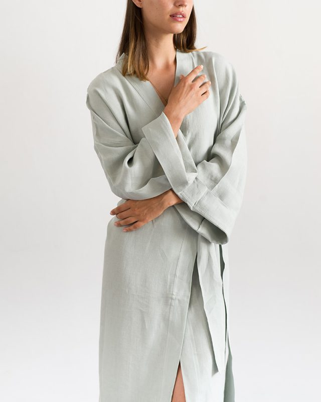 Woman posing with an all natural fibre Mungo Kamma Linen Gown in Moon Grey, one of the items in our apparel range.