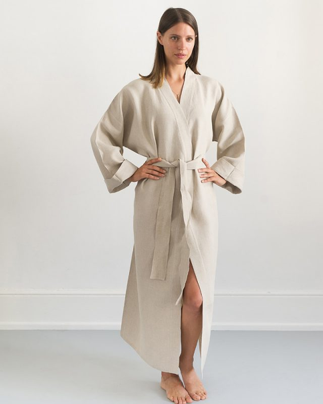 Woman posing with an all natural fibre Mungo Kamma Linen Gown in Natural, one of the items in our apparel range.