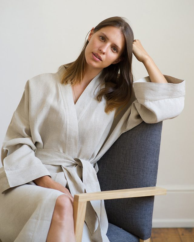 Woman on a chair wearing an all natural fibre Mungo Kamma Linen Gown in Natural.