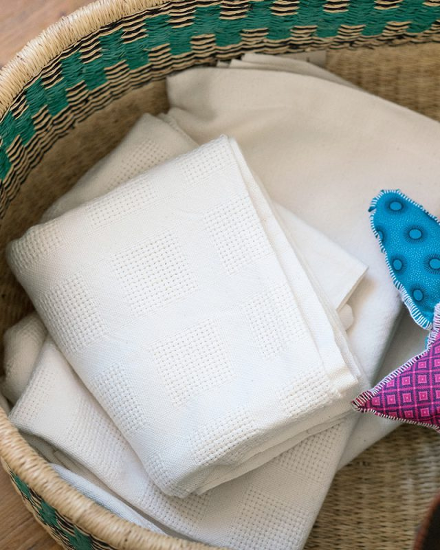 White Mungo organic cotton cot blankets in a baby basket