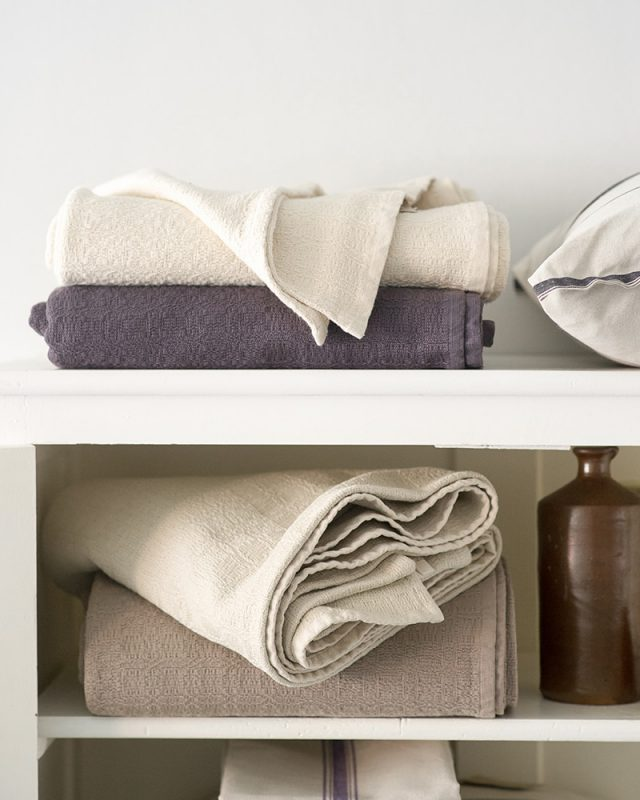 A stack of Mungo Cotton Cottonfields Blanket Throws on a shelf in Natural, Brown and Stone.