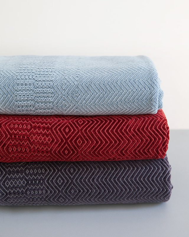 Mungo Kuba Zig Zag Cotton And Viscose Chenille Throws in Seamist Blue, Midnight Mole and Original Red.