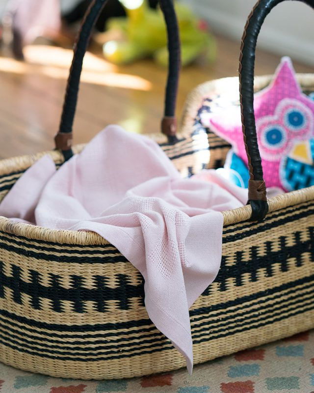 Mungo Organic Cotton Cot Baby Blanket in Pink in a woven moses basket with toy.