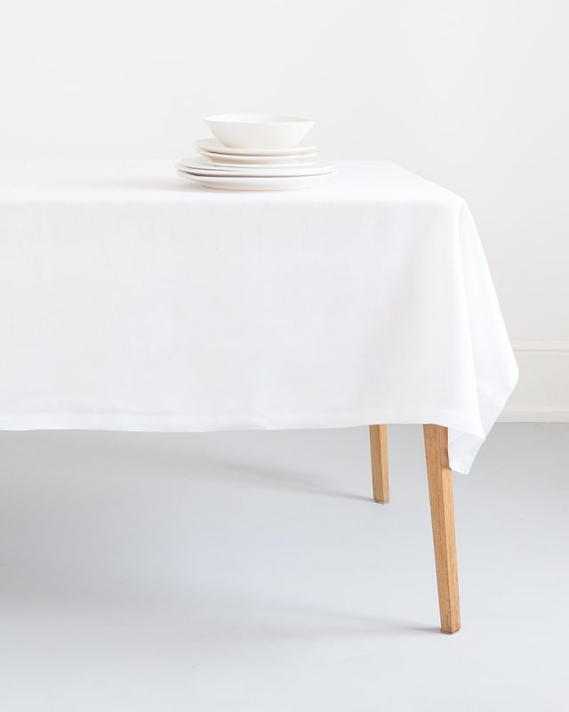 Mungo Linen Table Cloth in White set at a table with white crockery. Made with all natural fibres at our mill in Plettenberg Bay.