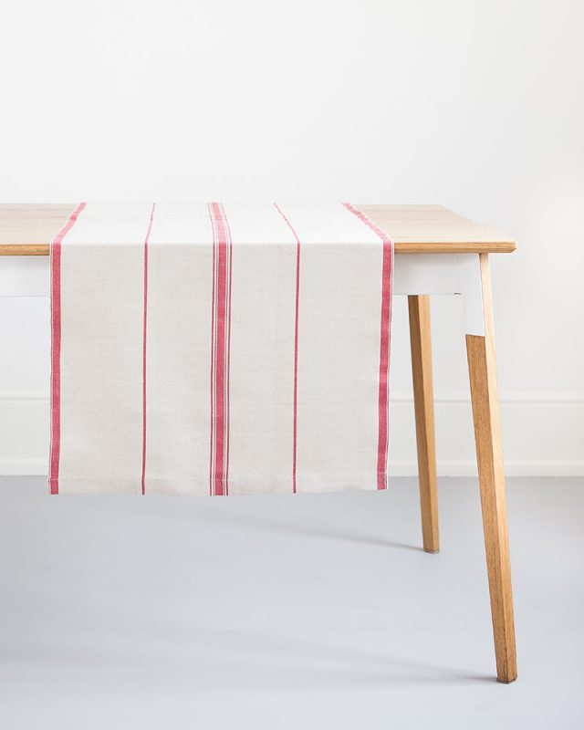 The Mungo Linen Lisburn Table Runner in Red hanging over a wooden table.