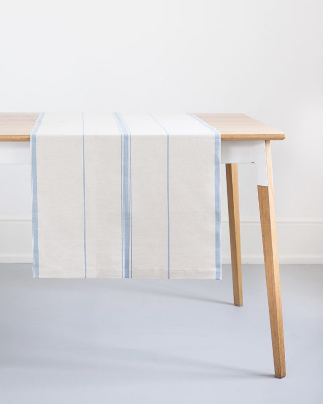 The Mungo Linen Lisburn Table Runner in Blue Bell hanging over a wooden table.