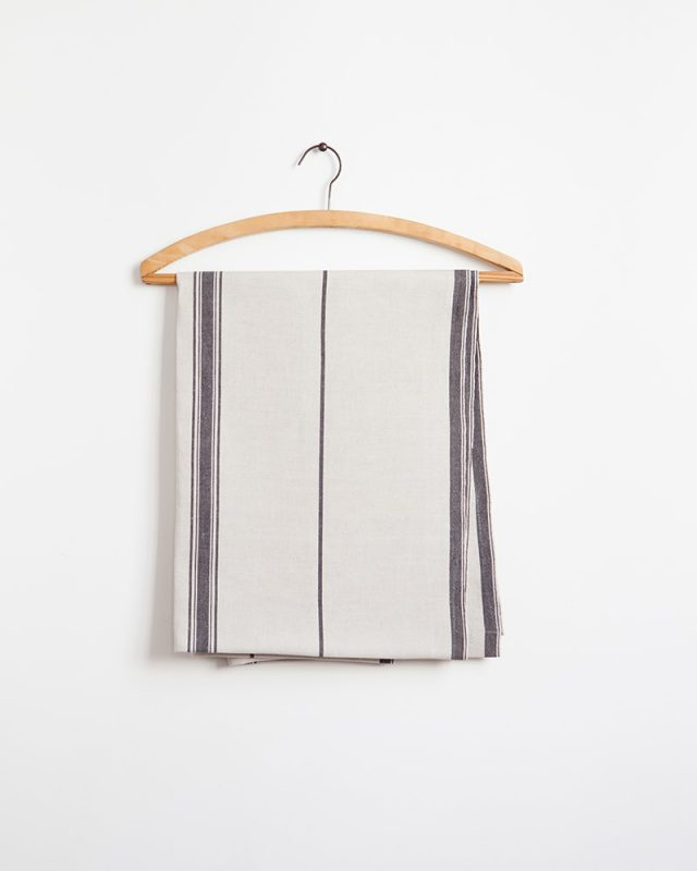 The Mungo Linen Lisburn Table Runner in French Navy, displayed here on a wooden hanger.