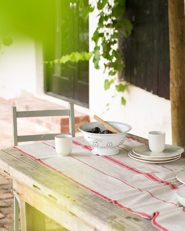 The Mungo Linen Lisburn Table Runner in Red set at an el fresco country table.