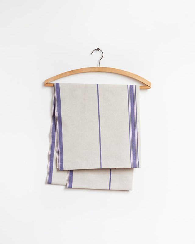 The Mungo Linen Lisburn Table Runner in All Blue, displayed here on a wooden hanger.