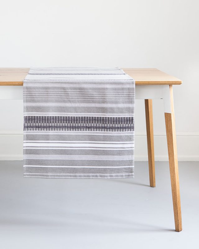 The Mungo Mali Linen Table Runner in Rolled Grey hanging over a wooden table