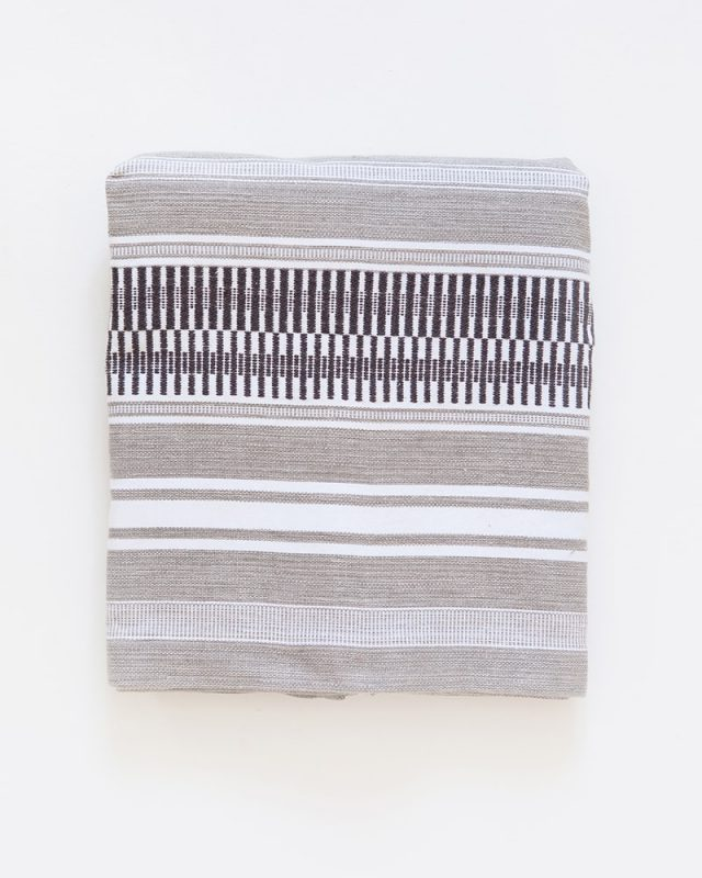 The Mungo Mali Linen Table Runner in Rolled Grey folded in a square.