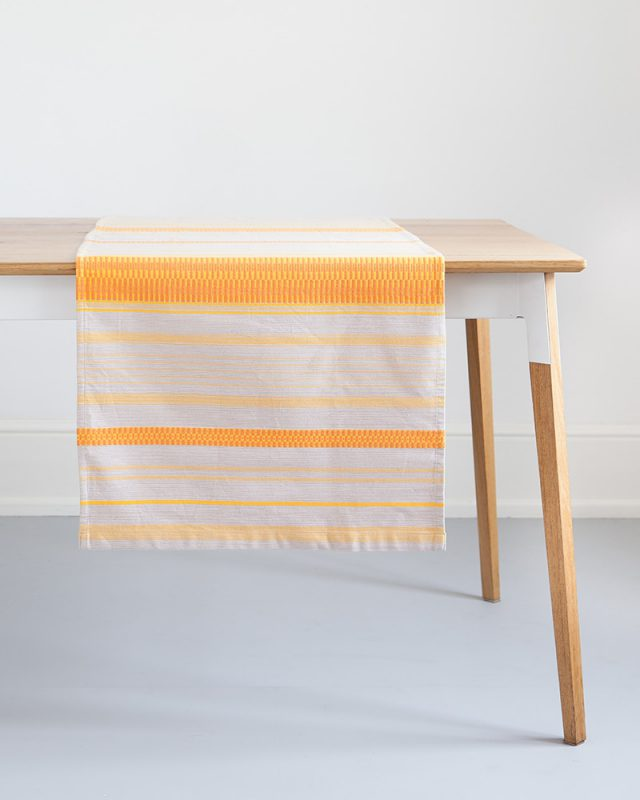 The Mungo Mali Linen Table Runner in Rolled Sand hanging over a wooden table