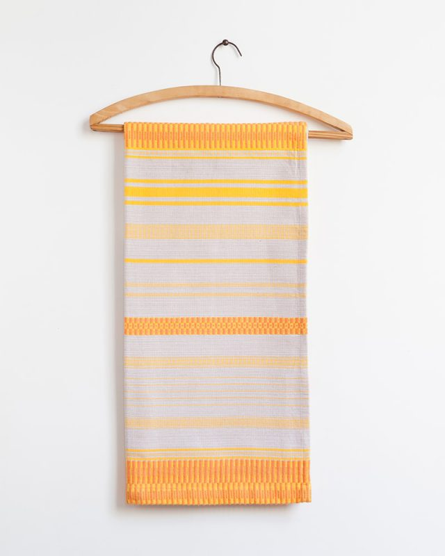 The Mungo Mali Linen Table Runner in Rolled Sand displayed on a wooden hanger