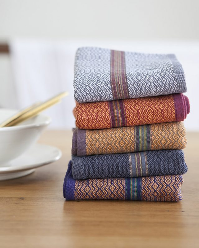 Mungo Table Linen Boma Napkins in White Stone, Orange Rust, Orange Sand, Black Indigo and Orange Indigo.