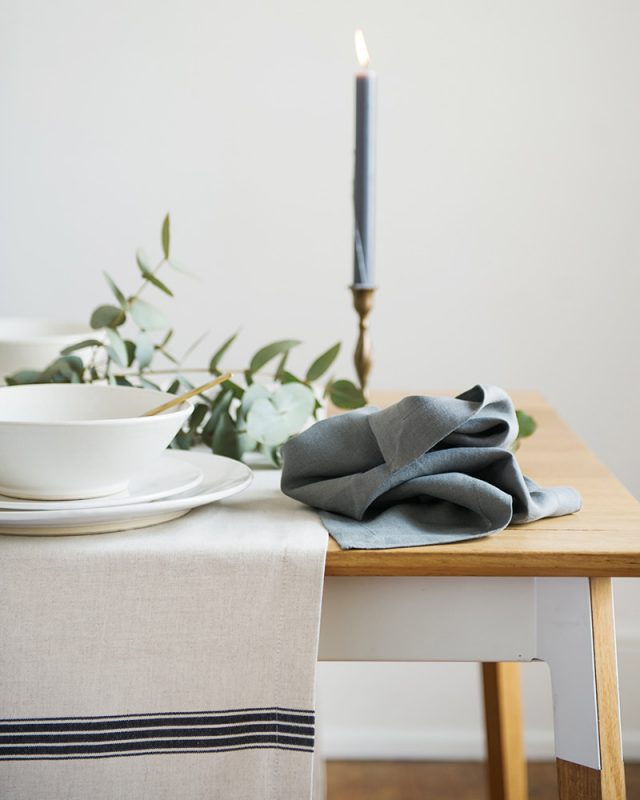 The Mungo Lisburn Linen Table Cloth in French Navy set at a table paired with a Fumo Linen Napkin and white crockery.