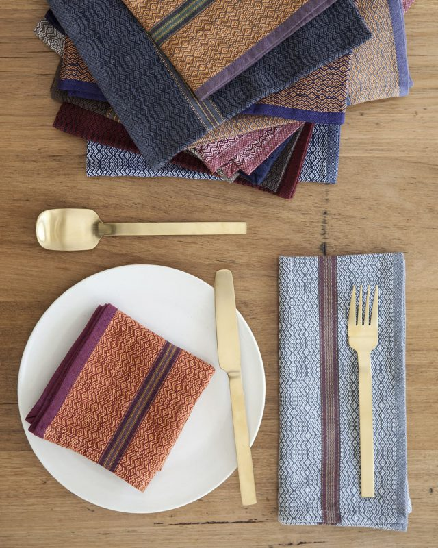The Mungo Boma cloth napkins are available in in a wide variety of colours, pictured here with gold cutlery and a white plate.