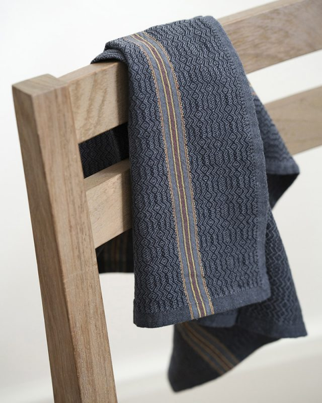 The Mungo boma cloth napkin is available in wide variety of colours - this one is black indigo hanging off of a chair. Find the one to suit your home.
