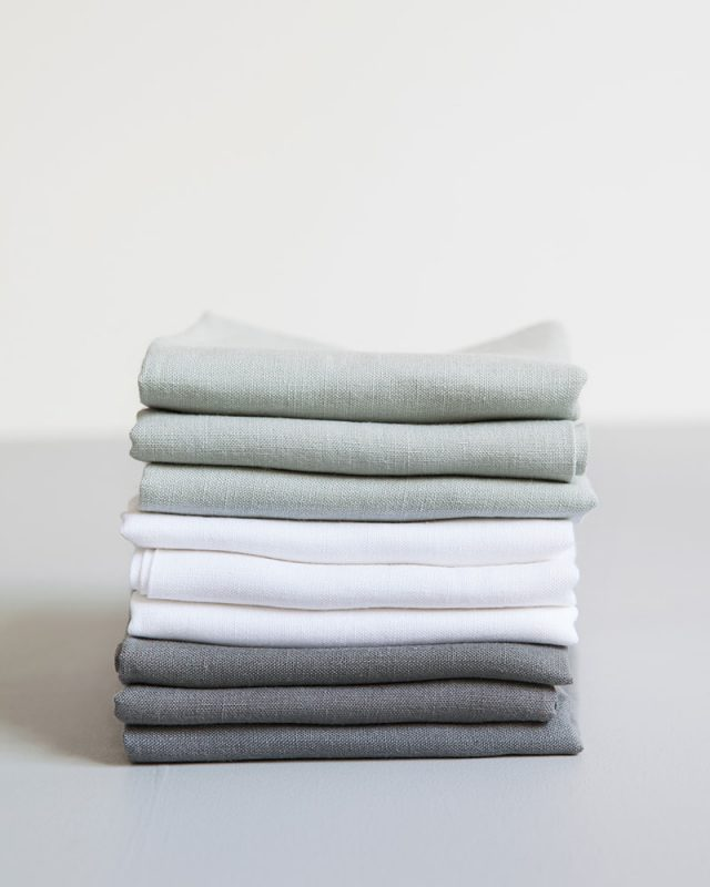 Stack of pure linen napkins come in Fumo Grey, Moon Grey and White, woven from Italian grown linen yarn at the Mungo Mill in Plettenberg Bay