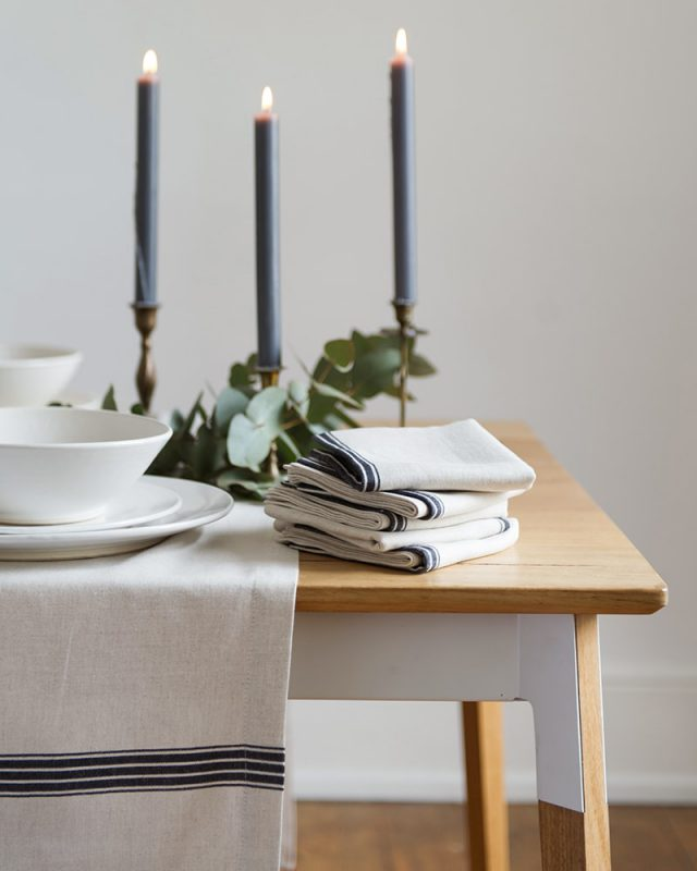 Candlit table setting featuring the provincial stripe tablecloths and napkins with a french navy stripe on a natural background