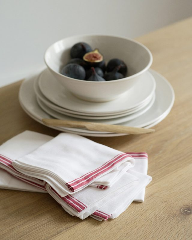 The Mungo Provincial Stripe Napkins in red on a natural and white background bring a french country charm to your table