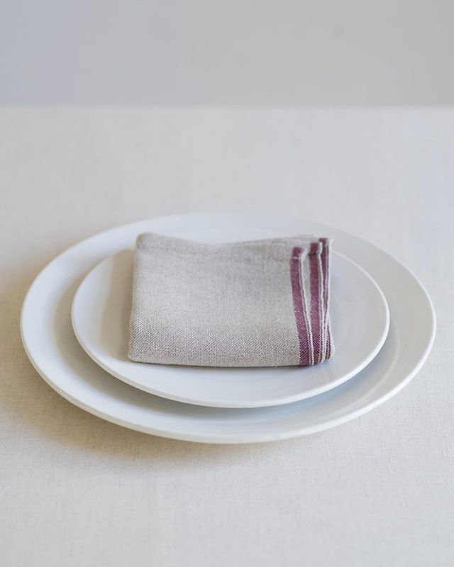 Mungo Natural Flax selvedge napkin with a burgundy stripe that runs down the true selvedge, woven of our antique looms in plettenberg bay