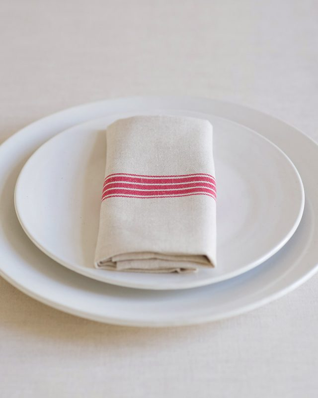 The Mungo provincial stripe napkin with a red stripe on a natural back, woven with cotton and linen, inspired by antique french grain sacking material