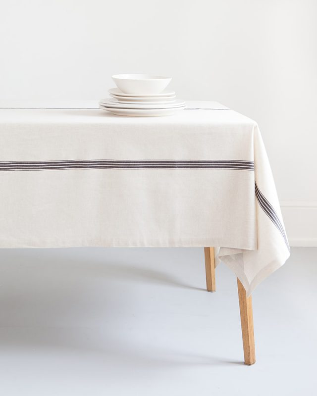 The Mungo Linen Provincial Stripe Table Cloth in French Navy and Natural, paired with white crockery for a crisp table setting.